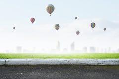 Aérostats volant au-dessus de la ville Photographie stock libre de droits