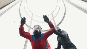 Aërodynamische buis De wind heft de persoon in rood kostuum op De trainer die hem helpen stock videobeelden
