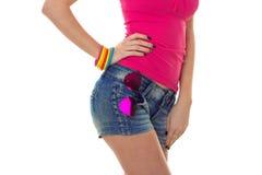 Aíslan al cuerpo de una muchacha hermosa joven en la camiseta rosada que guarda su mano en el lado en un fondo blanco Fotos de archivo libres de regalías
