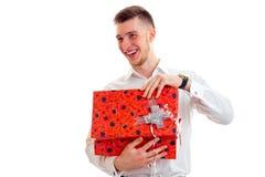 Aíslan al individuo gay hermoso en una camisa blanca que lleva a cabo un gran regalo y risas en un fondo blanco Fotos de archivo