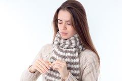 Aíslan a la chica joven con la bufanda y el suéter caliente en el fondo blanco Imágenes de archivo libres de regalías