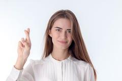 Aíslan a la chica joven en la blusa blanca que lleva a cabo la mano con los fingeres cruzados en fondo Foto de archivo libre de regalías