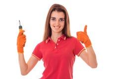 Aíslan a la chica joven sonriente en camisa roja y los guantes, sosteniéndose en su mano el dispositivo en un fondo blanco Fotografía de archivo