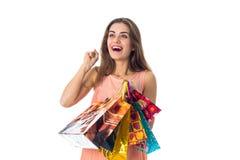 Aíslan a la muchacha de la diversión que lleva a cabo los paquetes coloridos con los regalos en un fondo blanco Foto de archivo libre de regalías