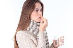 Aíslan a la muchacha en bufanda digno de lado y bebiendo la tableta en el fondo blanco Foto de archivo