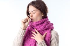 Aíslan a la muchacha en las toses calientes de una bufanda que cierran ojos en el fondo blanco Imagenes de archivo
