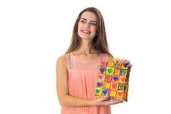 Aíslan a la muchacha Pin-para arriba criada en las manos del paquete del color con compras en un fondo blanco Imagen de archivo libre de regalías