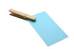 Aísle la abrazadera y el clip de madera con la nota de papel Imágenes de archivo libres de regalías