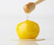 Aísle la miel orgánica de goteo con el limón en el fondo blanco Imagen de archivo