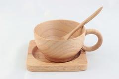 Aísle la taza de madera con la cuchara dentro en trey en el fondo blanco Fotografía de archivo