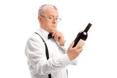 Aîné élégant lisant le label sur la bouteille de vin Photo libre de droits