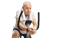 Aîné épuisé sur un vélo d'exercice Image stock