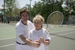 Aîné actif avec pro de tennis Image libre de droits