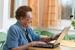 Aîné actif avec un ordinateur portatif dans les loisirs Images stock