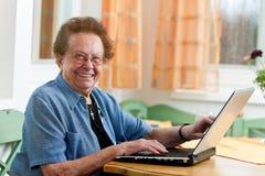 Aîné actif avec un ordinateur portatif dans les loisirs Image libre de droits