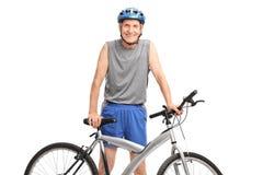 Aîné actif dans les vêtements de sport posant derrière une bicyclette Image stock