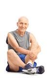 Aîné actif dans les vêtements de sport se reposant sur le plancher Photos stock