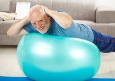 Aîné actif faisant des exercices sur la bille de gymnastique Photographie stock libre de droits