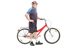 Aîné actif poussant une bicyclette et une pose Photo stock