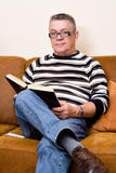Aîné affichant son livre sur le divan Photographie stock