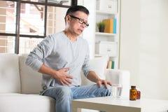 Aîné asiatique avec douleur abdominale image libre de droits