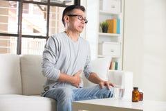 Aîné asiatique avec douleur abdominale Image stock