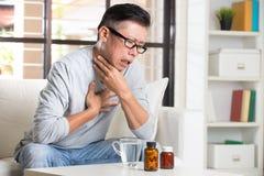 Aîné asiatique avec douleur de gorge Photo libre de droits