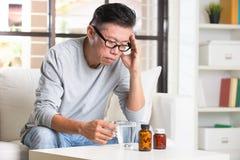 Aîné asiatique avec le mal de tête grave Photos stock