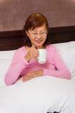 Aîné asiatique avec le thé dans le lit Photos libres de droits