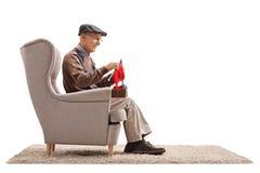 Aîné assis dans un tricotage de fauteuil Photo libre de droits