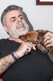 Aîné attirant avec la barbe blanche jouant avec le chien de teckel Image libre de droits