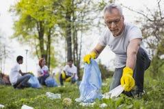 Aîné attirant volontaire prenant des déchets image stock