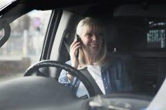 Aîné au téléphone dans la voiture Photographie stock libre de droits