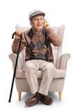 Aîné avec des paires des écouteurs et de la canne dans un fauteuil Images libres de droits