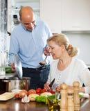 Aîné avec l'épouse mûre souriant et préparant la nourriture Image stock