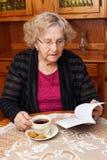 Aîné avec la lecture de thé Photographie stock