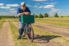 Aîné avec la valise verte étant prête pour monter sur une bicyclette sur une route de campagne Photographie stock
