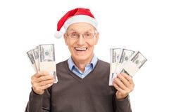 Aîné avec le chapeau de Santa tenant six piles d'argent Photo libre de droits