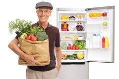 Aîné avec le sac plein des épiceries devant le réfrigérateur Images libres de droits