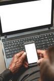 Aîné avec le téléphone et l'ordinateur portable Images libres de droits