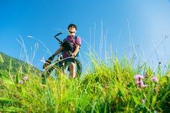 Aîné avec le vélo de montagne se tenant au sommet d'une colline Photo stock
