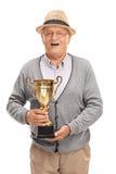 Aîné avec plaisir tenant un trophée d'or Image stock