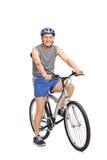 Aîné avec un casque bleu posant sur une bicyclette Photos stock