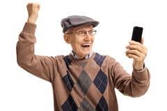 Aîné avec un téléphone faisant des gestes le bonheur Photographie stock