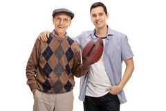 Aîné avec une boule de rugby et un jeune homme posant ensemble Images stock