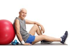 Aîné avec une boule et des haltères de pilates Image libre de droits