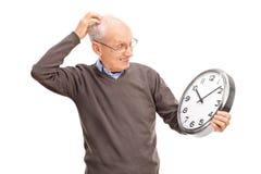 Aîné confus tenant une grande horloge murale Images stock