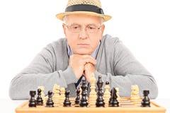 Aîné contemplant sa prochaine étape en partie d'échecs Image libre de droits