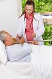 Aîné dans l'hôpital prenant la médecine Image libre de droits