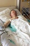 Aîné dans la verticale de lit d'hôpital Photos stock